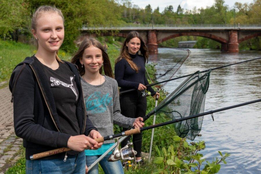 Josephine und Malin (sie gehören zu einem Hausstand) und Janina (v. l.) gehen regelmäßig angeln. Zum Fototermin an der Zwickauer Mulde in Lunzenau war Angeln wegen des hohen Wasserstandes nicht möglich.
