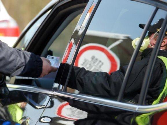 Ein Polizist mit Atemschutzmaske kontrolliert ein Auto an der tschechisch-deutschen Grenze.