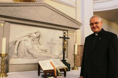 Pfarrer Frank Pierel am Altar der Pausaer Kirche. Die Pieta veranschaulicht, wie Christus vom Kreuz genommen und von Maria gehalten wird. Sogar im Kunstführer der DDR war Pausa mit dieser Pieta vertreten.