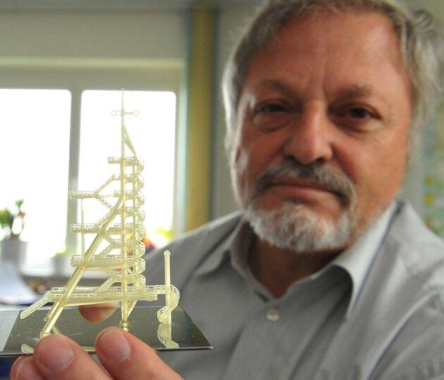 CAP-Chef Wolfgang Meyer mit einem filigranen Kunststoffmodell des Oelsnitzer Glückaufturms. Gefertigt im sogenannten Rapid-Prototyping-Verfahren, steht es auf einer plasmapolierten Fläche. Beide Technologien sind im CAP zu Hause.