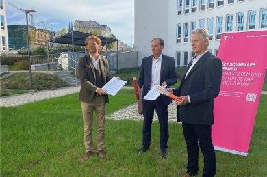 Baubürgermeister Michael Stötzer (links), Regionalmanager Hendrik König (Mitte) Projektleiter Matthias Patzsch - beide von der Deutschen Telekom - haben eine Vereinbarung über den weiteren Ausbau des Glasfasernetzes in Chemnitz geschlossen.