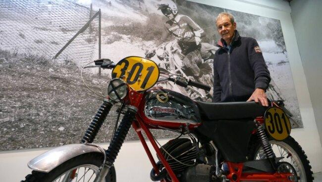 Im Museum hängen erste große Banner. Hier steht Eberhard Weber, der Vorsitzende des Fördervereins, samt originaler Zündapp-Maschine vor einem Bild, das ihn bei den Six Days 1974 in Italien zeigt.