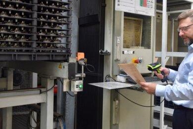 Vacuheat-Geschäftsführer Bert Reinhold in seiner Produktionshalle. Mittels Scanner werden alle nötigen Informationen über die Bauteile, die in die Vakuumöfen kommen, aufgenommen.
