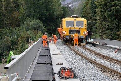 Mit einer sogenannten Gleisstopfmaschine wurde der Schotter unter und neben den Gleisen verdichtet. Links im Bild sind Mitarbeiter des Unternehmens dabei, die Gangstege und Geländer auszurichten und zu befestigen.