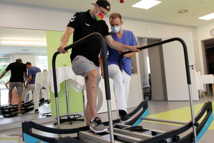 EHV-Handballer Kevin Roch testet mit Therapeut Toni Illig ein Gerät, auf dem Arme und Beine gleichzeitig in Bewegung geraten.