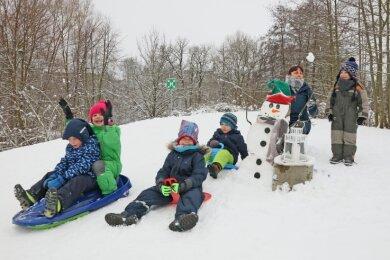 Der Schneemann auf dem Rodelberg hinter der Kita bekommt nicht nur von Rallye-Teilnehmern, sondern auch Schlittenfahrern Besuch.