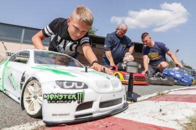 Die Autos sind bereit: Vereinschef Michael Opel (Mitte) und die zwei Nachwuchsfahrer Lucien Neubert (links) und Eric Löbling fiebern dem ersten echten Nacht-Rennen im Mühlauer Minidrom entgegen. Die ferngesteuerten Autos im Maßstab 1:8 oder 1:5 erreichen bis zu 80 km/h.