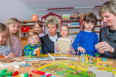 Die Leiterin der Kita Villa Kunterbunt in Aue, Linda Habekus, inmitten der Kinder Paulina, Johanna, Robert, Liesbeth, Sophie und Melissa. Die 64-Jährige übergibt die Leitung der Einrichtung an Jane Unger (rechts).