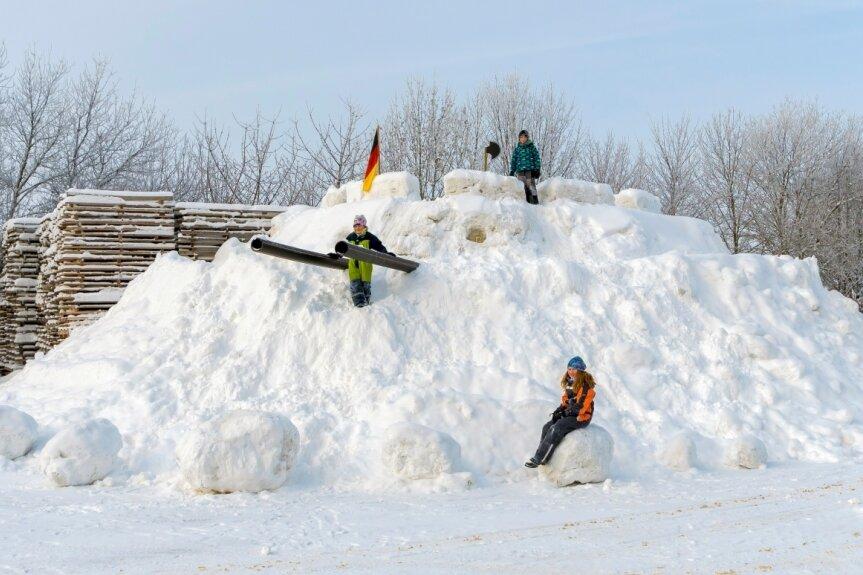 Winterzauber: Schneeburg auf Firmengelände und Weihnachtsbaum mit Eiskleid