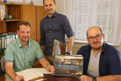 Hauptverfasser Patrick Bochmann, Ortsvorsteher Lutz Weißpflug und der neue Rödlitzer Ortschronist Axel Höfer (v.l.) präsentieren die Mammutchronik. Diese enthält nicht nur Text, sondern auch viele Bilder.