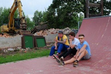 """Fabio Westerhof und Maurice Schiek unterstützen Streetworker Holger """"Fritz"""" Junghans (von rechts) bei der Bauplanung und der Koordination der insgesamt etwa einem Dutzend jugendlichen Helfer. Hier wird gerade die Beschaffung des Baumaterials für die Rampe besprochen."""