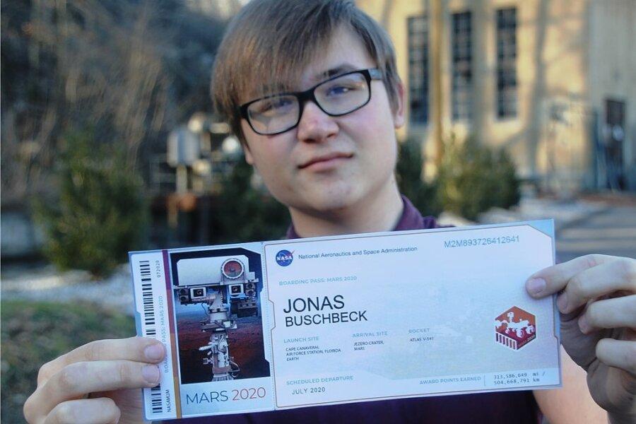 Weltraumfan Jonas Buschbeck aus Erdmannsdorf zeigt seinem symbolischen Boarding-Pass für eine Reise auf den Mars. Sein Name ist auf einem Chip gespeichert, der in einen im Februar auf dem Planeten gelandeten Rover integriert ist.