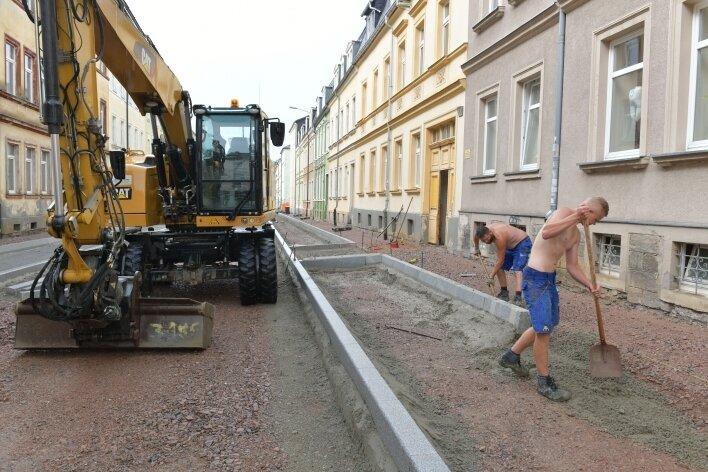 In der Humboldtstraße in Freiberg setzen Mitarbeiter der Firma Andreas Adam derzeit Bordsteine für den Fußweg.