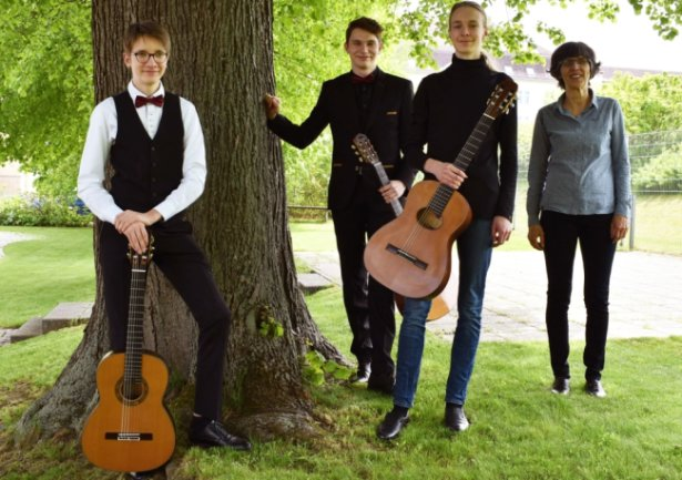 """Marko Dorotsky, Theodor Dorotsky und Jaron Rittmeister (v. l.), hier mit ihrer Gitarrenlehrerin Martina Bunk, erspielten sich vordere Plätze im Bundeswettbewerb """"Jugend musiziert""""."""