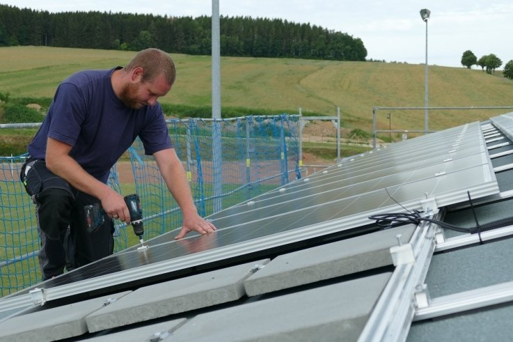 Sören Rösch bei der Arbeit auf dem Dach des Drebacher Sportlerheims.60 Fotovoltaik-Module wurden dort installiert.