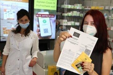 Kundin Leonie Löffler mit dem digitalen Impfpass, den ihr Mitarbeiterin Jana Buschwerk in der City-Apotheke Hohenstein-Ernstthal ausgedruckt hat.