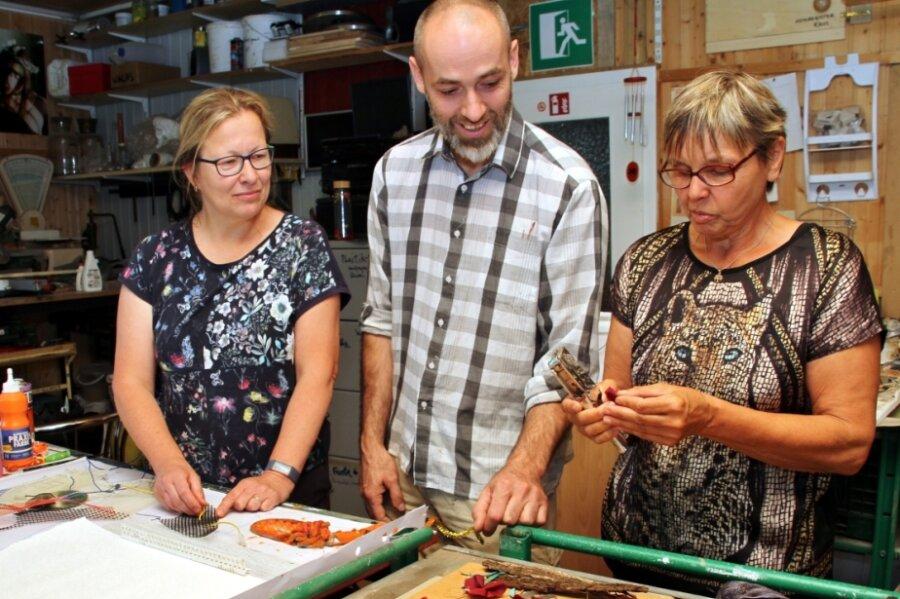 Jens Ossada gibt Ulrike Krause (l.) und Regine Krätzschmar Hinweise zur Gestaltung der Materialbilder. Dieser Workshop der Sommerakademie findet im Refugium Ehrenberg statt.
