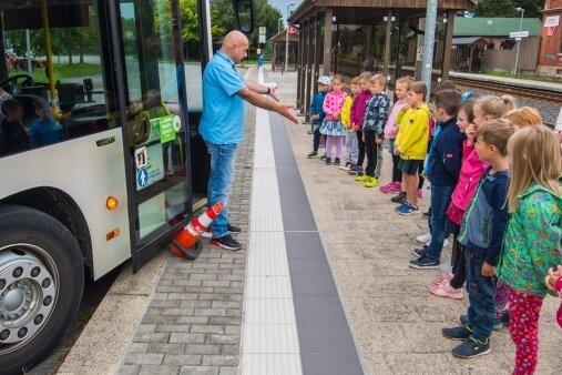 Wer zu nah an der Straße auf den Bus wartet, dem könnte es wie dem Verkehrskegel im Foto ergehen. Busfahrer Steffen Schukat erklärt den Schülern der Klasse 1a aus Jahnsdorf, wie man sich richtig verhält.