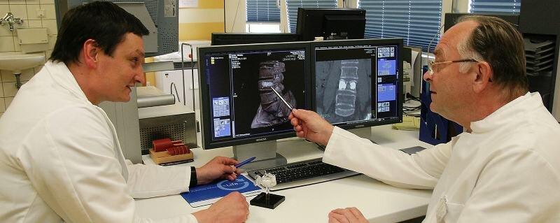 Die beiden Chefärzte Udo Raab (Radiologie) und Günter Schmoz (Chirurgie) sehen sich am Monitor das Ergebnis der kyphoplastischen Behandlung einer Wirbelsäulenverletzung an. Deutlich erkennbar die Stellen, an den Knochenzement die Wirbelkörper wieder stabilisiert.
