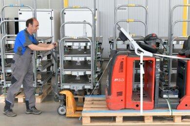 Mirko Hammerl stellt in der einstigen Logistikhalle der insolventen Solarworld einen Elektrolastschlepper und Transportwagen bereit. Die komplette Versteigerungsliste steht unter aswgmbh.com im Internet.