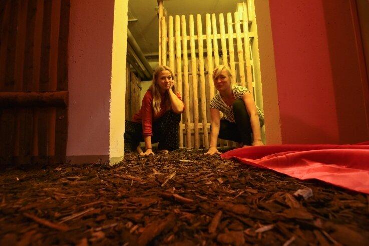 """Juliane Meckert (links) und Nadja Hoppe haben im Keller Holzschnitzel und Torf verteilt. Die so entstandene """"Keimzelle"""" ist ein Ort ihrer Performance mit drei Akten."""