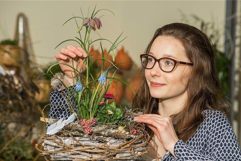 Fertig: Mit Leim und Draht verbindet Sophie Pfeiffer den bepflanzten Tontopf mit dem Holzkranz. Verfeinert mit Clematisranken, Birkenzweigen, Pfeffer, Federn und Eiern ist der Osterschmuck perfekt.