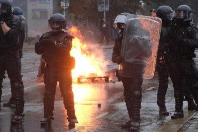 Polizisten stehen an einer brennenden Barrikade im Stadtteil Connewitz.