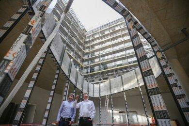 Der Bau des Firmensitzes des Versorgers Eins an der Ecke Bahnhofstraße/Johannisplatz ist die derzeit größte Baustelle der City. Thomas Frank (rechts), Geschäftsführer der verantwortlichen Projektentwicklungsfirma, und Thomas Knorn von der Baufirma Köster stehen im Lichthof des Foyers.