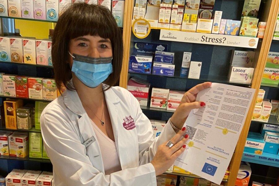 Uta Siling, Inhaberin der Rats- sowie der Stadt- und Löwenapotheke, zeigt einen Ausdruck für den digitalen Impfnachweis.