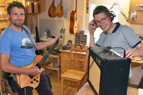 Roy Fankhänel (links) aus Oelsnitz und Tim Walter aus Burgstädt haben die Gitarrenmanufaktur Odem gegründet. Das neue Teil wird schon mal in der Werkstatt ausprobiert.