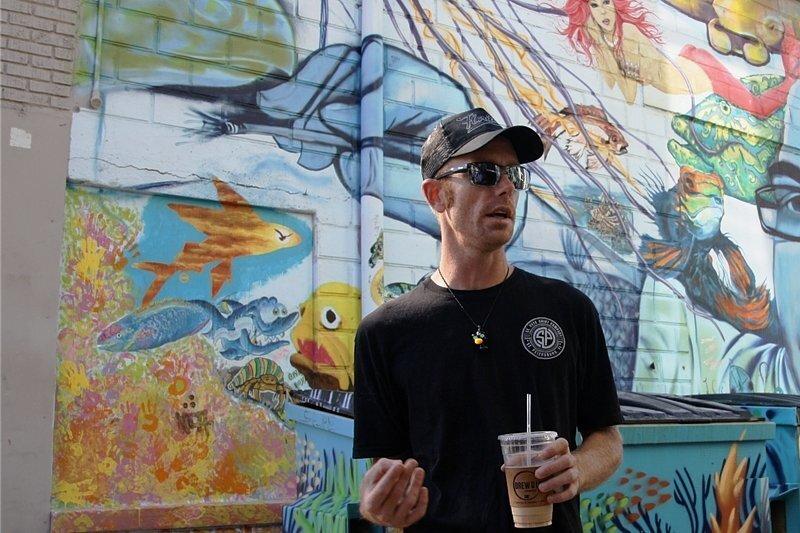 """Derek Donnelly vor einer Wand, auf der und seine Kollegen ihren verstorbenen Künstlerkumpel Bill """"Woo"""" Correira verewigt haben."""