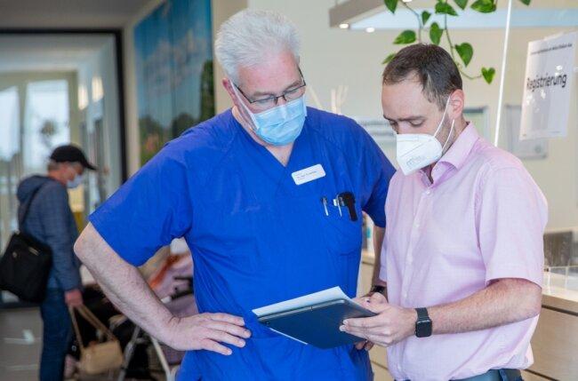 """Chefarzt Thomas Ketteler (links) und Sascha Goll, Leiter des Krisenstabes """"Kommunale Impfhilfe"""" der Stadt Aue-Bad Schlema, besprechen die anstehenden Impfungen. Dem Helios-Klinikum stehen Dosen für insgesamt 1950 Menschen zur Verfügung."""