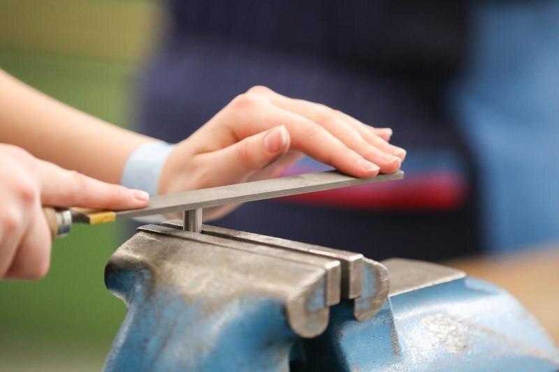 Eine Auszubildende feilt an einem Werkstück im Mechanik-Raum im Ausbildungszentrum im BMW-Werk.