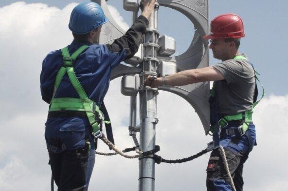 Sirenen moderner Bauart ermöglichen neben verschiedenen Signaltönen auch Durchsagen. Im Bild: Mitarbeiter einer Firma montieren eine elektronische Sirene auf dem Dach einer Schule.