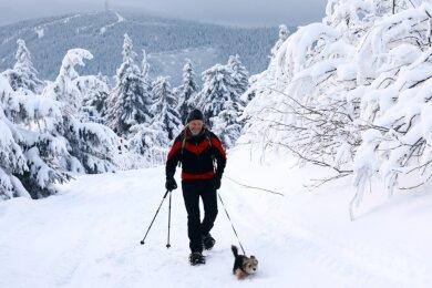 Der Winter bietet derzeit viele Facetten. Hobbysportler Mike Pyritz aus Oberwiesenthal genießt die Idylle beispielsweise beim Anstieg in Begleitung von Hündin Iljana. Der 47-Jährige, der sonst auf Skiern und im Sommer oft auf dem Mountainbike anzutreffen ist, schlittert später mit Blick auf den Keilberg wieder den Hang hinab.