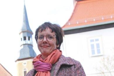 Pfarrerin Astrid Reglitz vor der Siebenlehner Kirche und dem Pfarrhaus.