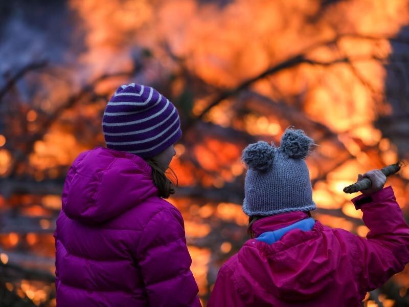 Zwei Mädchen stehen vor einem Osterfeuer.