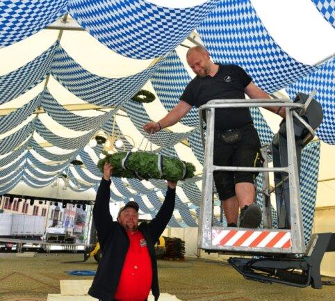 René Kutzke (l.) und Maik Richter haben am Donnerstag beim Aufbau und Schmücken für das Oktoberfest in Mittweida kräftig mit angepackt.