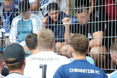 Stein des Anstoßes: Daniel Frahn (mit verkehrt aufgesetztem Basecap hinterm Zaun) im Gästeblock vor seiner Mannschaft, die 1:3 in Halle verlor. Er habe dort Sympathien zu führenden Köpfen rechtsgesinnter Gruppierungen offenkundig zur Schau gestellt, heißt es bei der CFC GmbH.