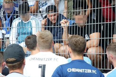 Daniel Frahn (mit verkehrt aufgesetztem Basecap hinterm Zaun) im Gästeblock vor seiner Mannschaft, die 1:3 in Halle verlor. Er habe dort Sympathien zu führenden Köpfen rechtsgesinnter Gruppierungen offenkundig zur Schau gestellt, so die CFC GmbH.