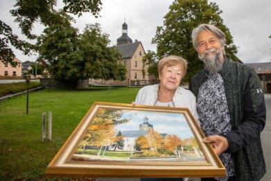 Christina Schneider übergibt das Gemälde ihres verstorbenen Mannes als Geschenk an die Gemeinde. Bürgermeister Ulrich Sörgel nimmt es dankbar entgegen und verspricht, dass es einen Ehrenplatz erhält.