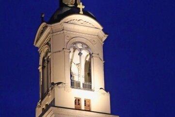Der Kirchturm wird in den Abendstunden angeleuchtet.