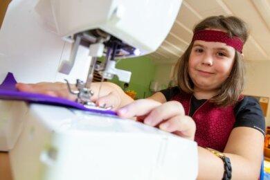 Die siebenjährige Emily sitzt in der Kinderstadt an der Nähmaschine. Hergestellt wird eine Wimpelkette.