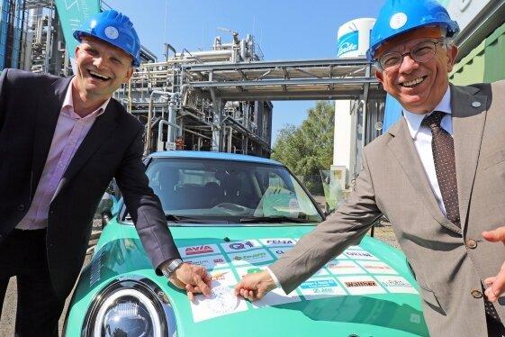 Prof. Martin Gräbner (l.) und Prof. Klaus-Dieter Barbknecht, Rektor der TU Bergakademie Freiberg, verewigen das Logo der Ressourcenuniversität auf dem e-Fuels-Fahrzeug.