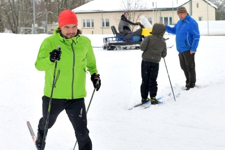 Rund um Linda in die Loipe: Am Sportplatz des SV Linda haben die Funktionäre um Frank Pfeifer sowie Sohn Robin (auf dem Schneemobil) und Vereinschef Mirko Espig (r.) mehrere Loipen gespurt.