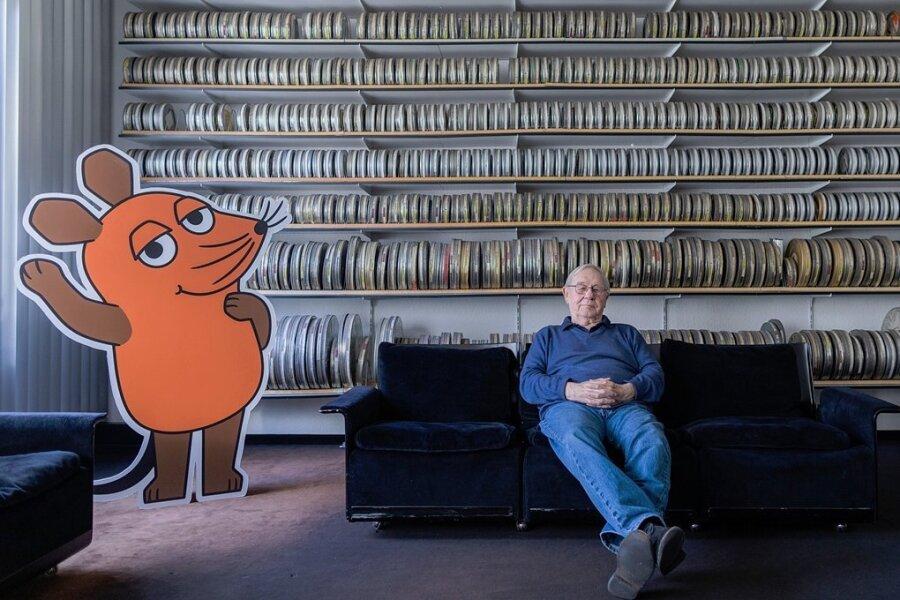 """Armin Maiwald, Filmemacher, Autor und Miterfinder der """"Sendung mit der Maus"""", sitzt auf einem Sofa in seinem Büro vor zahlreichen Filmrollen. Bis heute wirkt der 81-Jährige an jeder Sendung mit."""