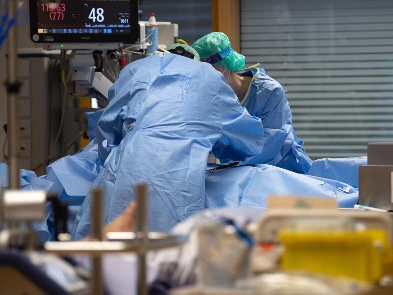 Medizinisches Personal legt auf einer Intensivstation einem Covid-19-Patienten einen Zugang für die künstliche Beatmung.