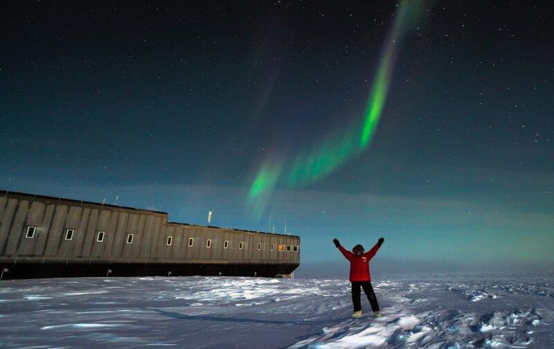 Polarlichter fotografieren. Das macht der Erdmannsdorfer Martin Wolf gerne in seiner Freizeit am Südpol. Hier ein Selbstporträt mit seiner Arbeitsstelle im Hintergrund: die Amundsen-Scott-Antarktisstation.
