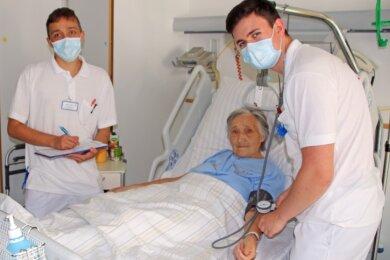 Nicolas Badura (r.), Karolin Fischer und Alexander Schubert messen den Blutdruck bei Patientin Ursula Wohlert auf Station 9 des Kreiskrankenhauses in Freiberg.