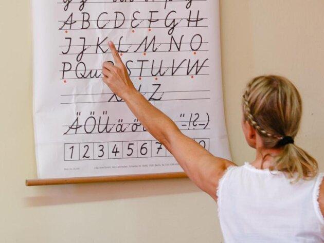 Eine Lehrerin zeigt auf eine Buchstabentafel im Klassenzimmer ihrer Grundschule.
